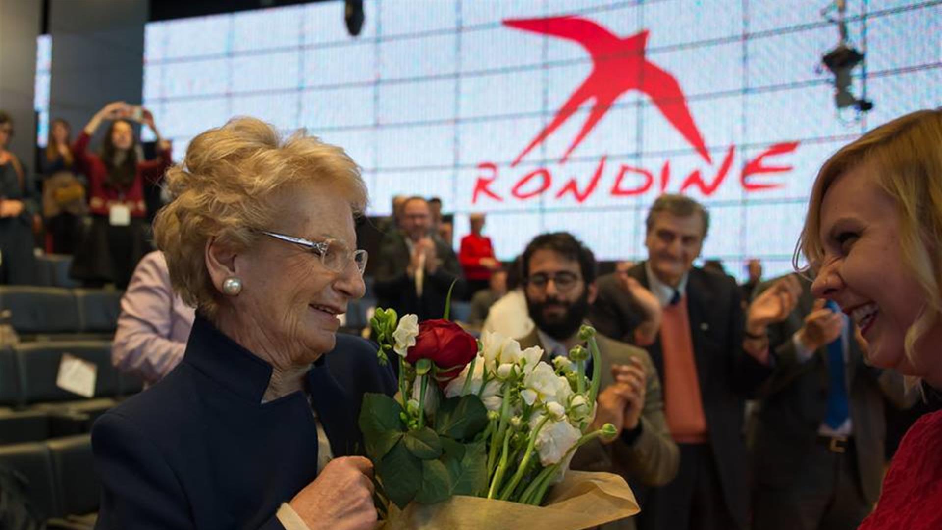 Liliana Segre con fiori e sullo sfondo logo rondine